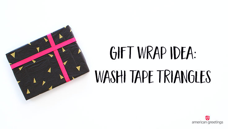 A gift wrapped in black wrapping paper with yellow triangle decorations and pink ribbon -