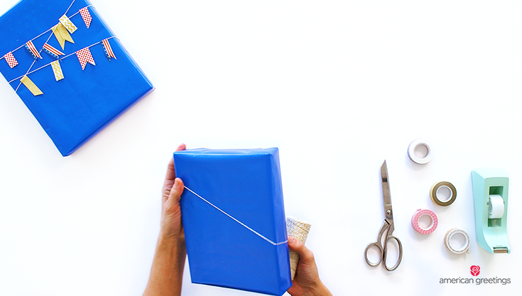 Step 1 illustrated with hands adding the twine to the blue gift box