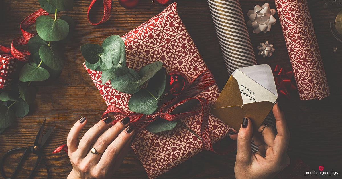 Hands wrapping a gift with Christmas themed paper and decorations