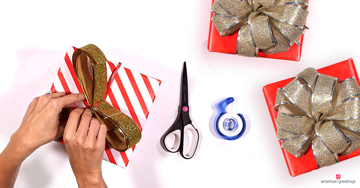 Hands tying a bow on a red and white gift wrapped box; next to two festive wrapped boxes, including sparkly handcrafted bows. and scissors and tape