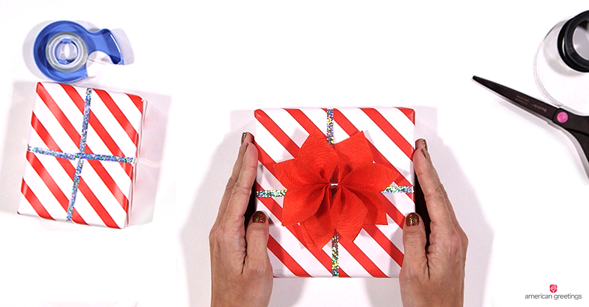 Hands holding small box wrapped in striped paper with a handcrafted poinsetta shaped bow