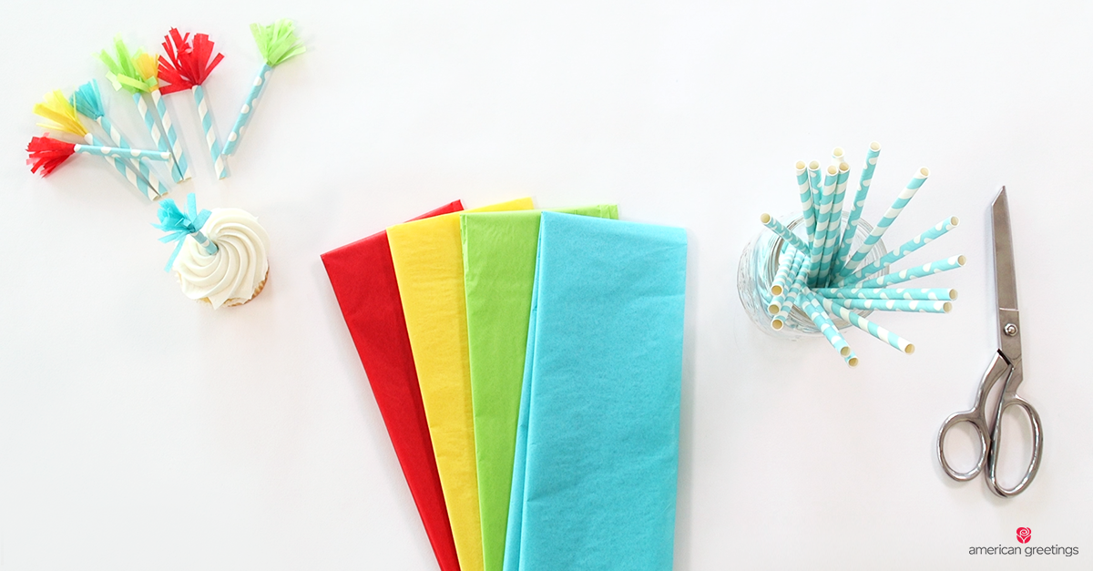Colorful straws with colored tissue paper tassles on the end, one is in a cupcake as a decoration. nearby are scissors, colored tissue paper, and straws ready to make more.