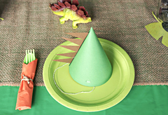 Party place setting with dinosaur party hat and toy dinosaur
