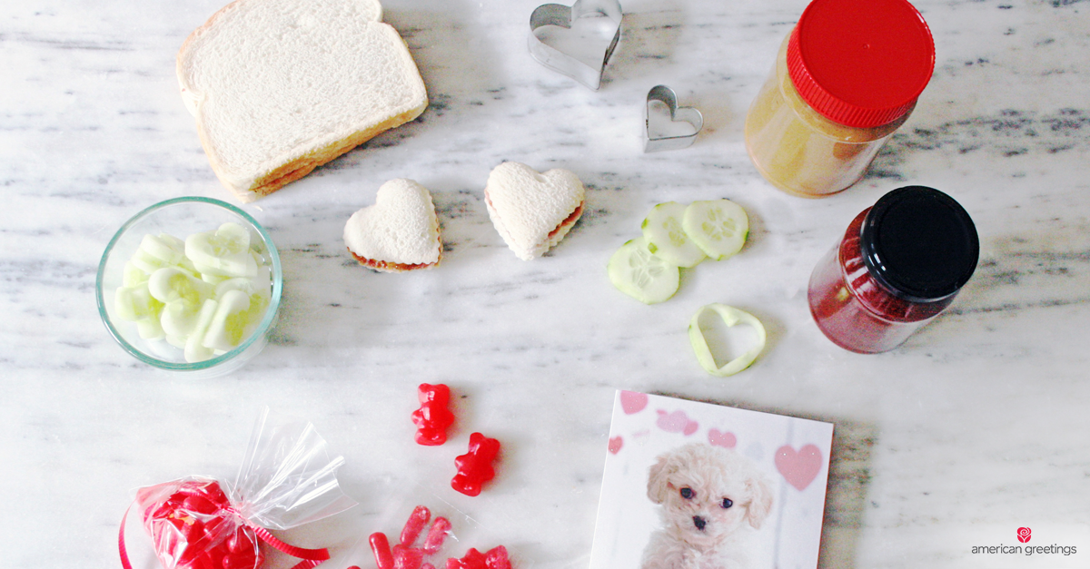 Valentine's lunchbox supplies to make heart shaped sandwiches for kids valentines day lunch: heart cookie cutters, peanut butter, jelly, red candy and Valentine's Day card