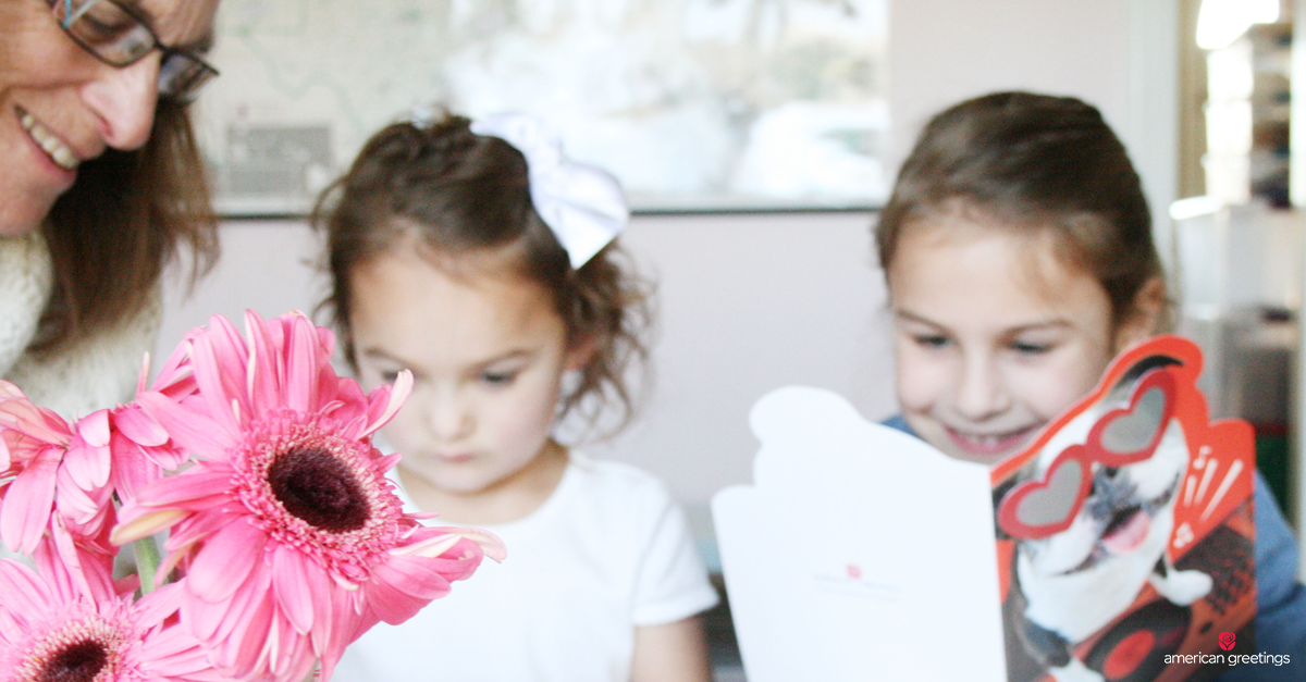 Grandparent and grandchildren making Valentine's Day crafts and reading Valentine's Day cards - pink daisies