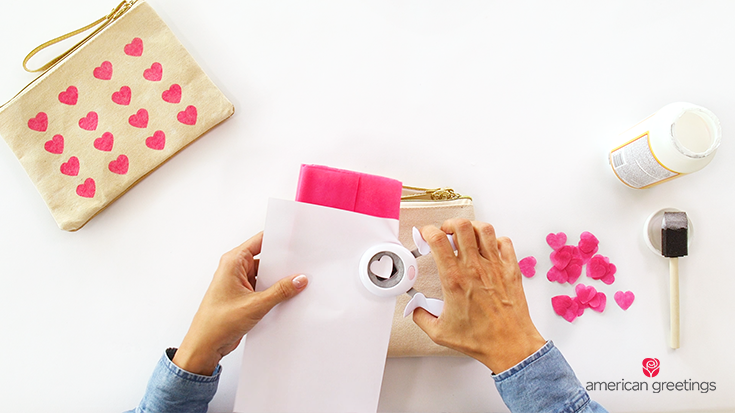 Step 2 - Cut the tissue paper by keeping it folded between the sheet of regular paper so you get more hearts out of one punch