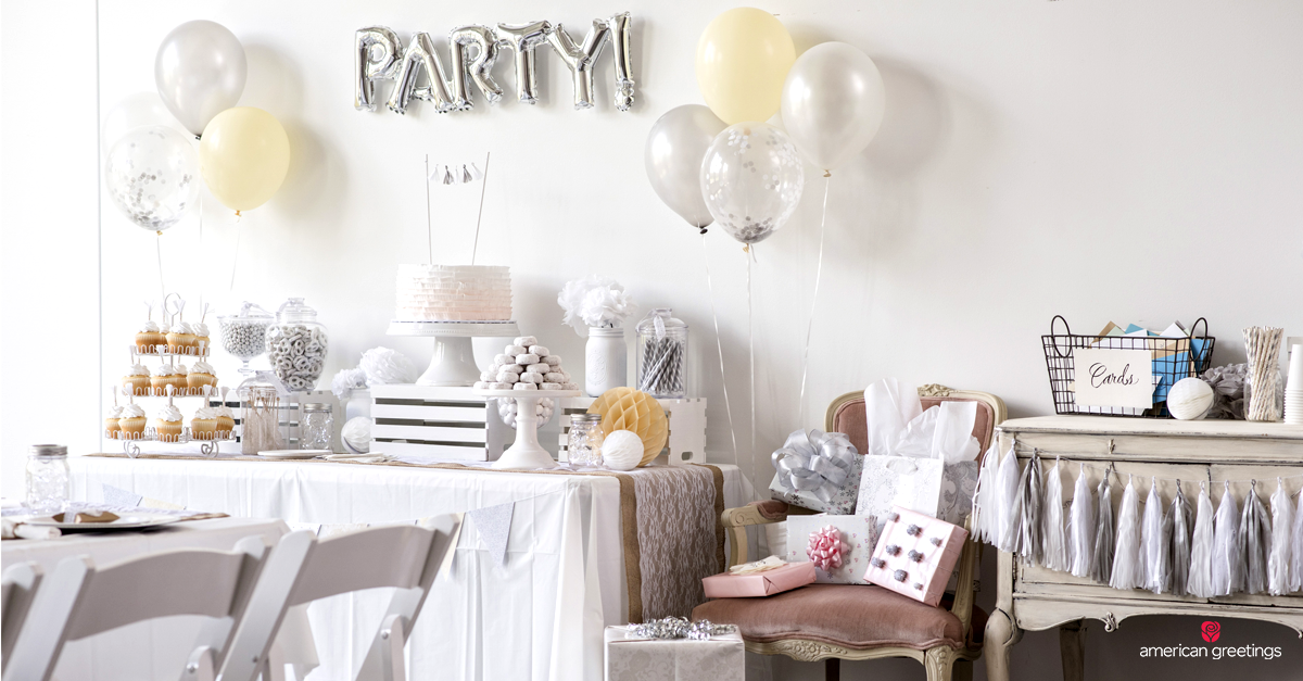 Table set with a white table cloth, white birthday cake, white and silver balloons, and an inflatable balloon with the word