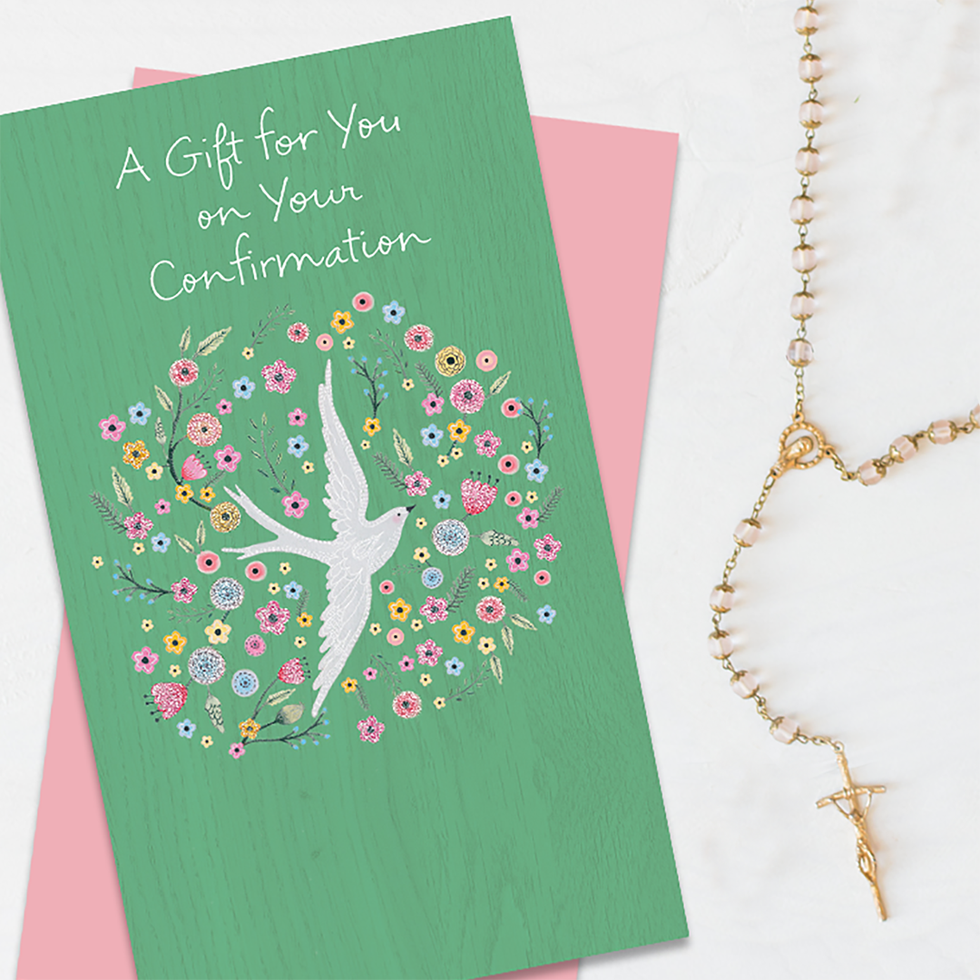 A green confirmation card with a dove and flowers illustration and placed on top of a pink card next to roasary beads.