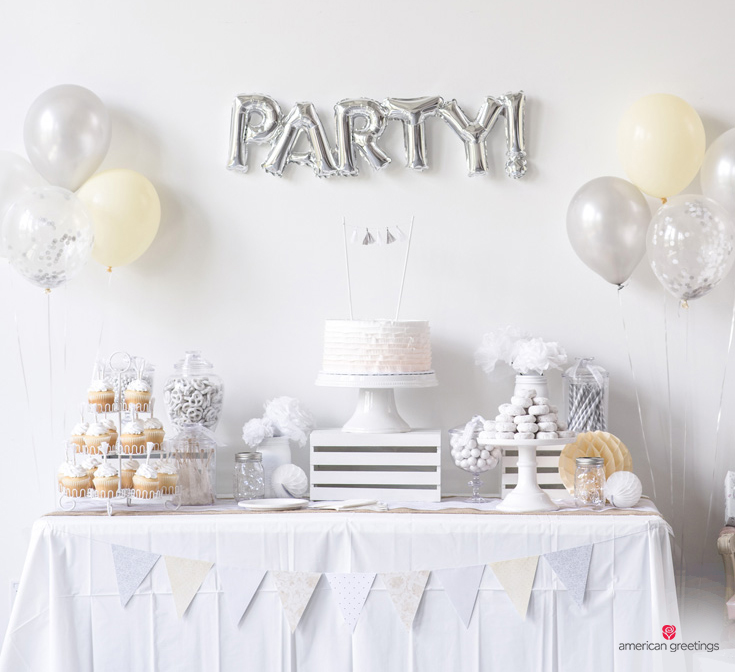 A picture of a white party table complete with white cupcakes, white paper flowers,donuts, and chocolate pretzels placed on a white tablecloth decorated with a white triangle banner and balloons.
