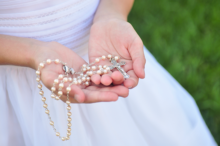 A close up a a girl in a white confirmation dress holding rosary beads.
