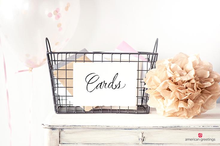Card basket near a tissue paper pom-pom