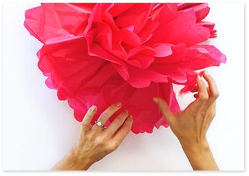 Hands making tissue paper pom poms