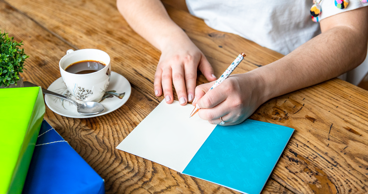 Image with a woman writing a congrats card while having a coffee