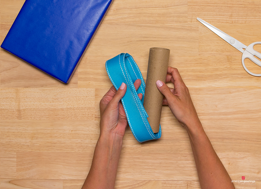 Step 4 - Hold on to the ribbon with one hand and carefully remove the paper towel roll with the other