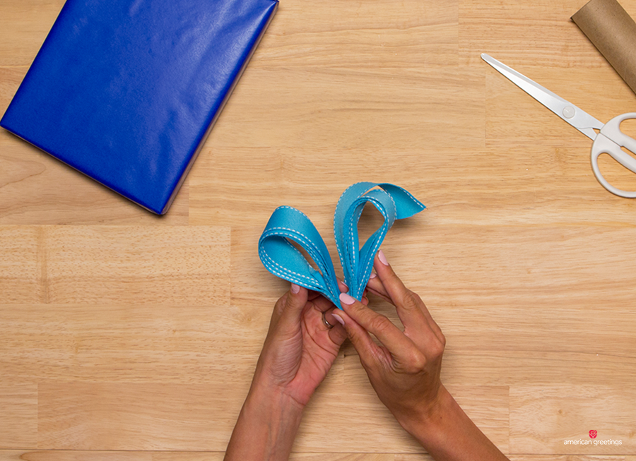 Step 5 - fold both sides of the ribbon toward each other to find the middle