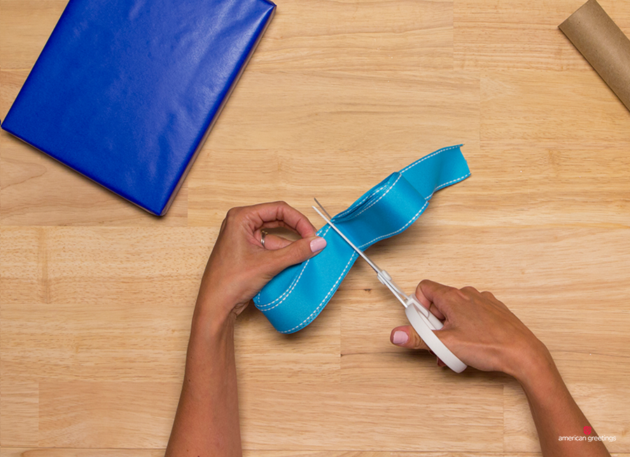 Step 6 - Use the scissors to cut a small slit on one side of the ribbon, about 1/3 of the way through