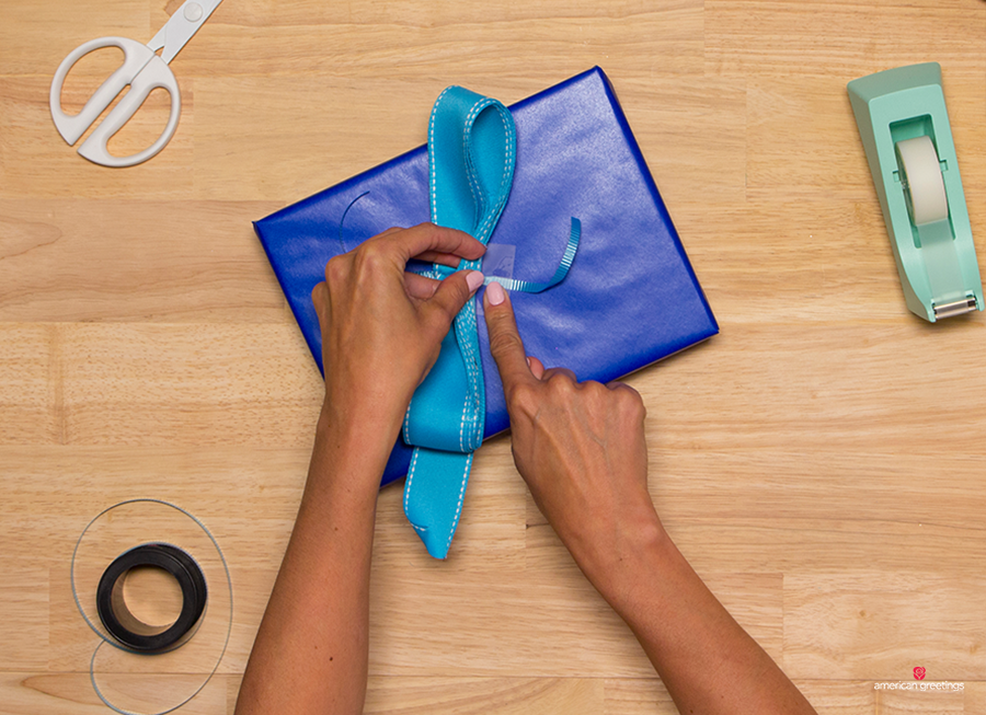 Step 11 - Tape the ends of the curling ribbon to your gift to attach the bow, then cut off any excess ribbon