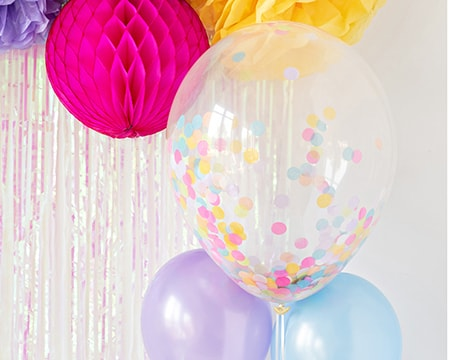 Confetti Balloons and Pom Poms Decorations against a shimmery wall.