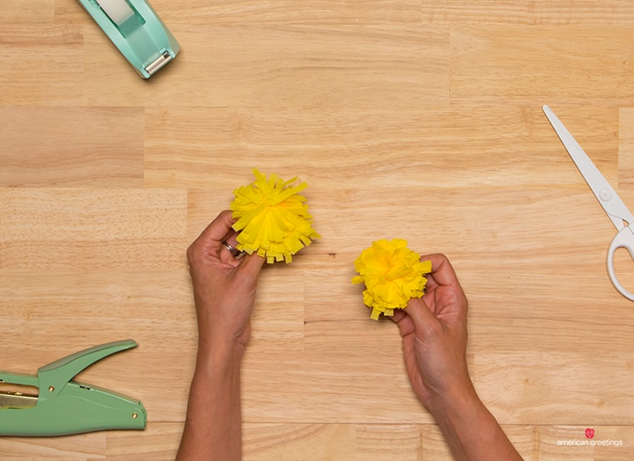 image with hands holding the smaller and thebigger dandelion