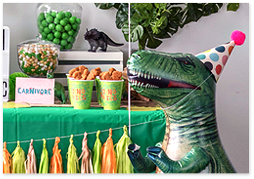 Dinosaur balloon with a party hat next to a green table decorated with tissue paper garlands, green candy jar, cups with snacks.