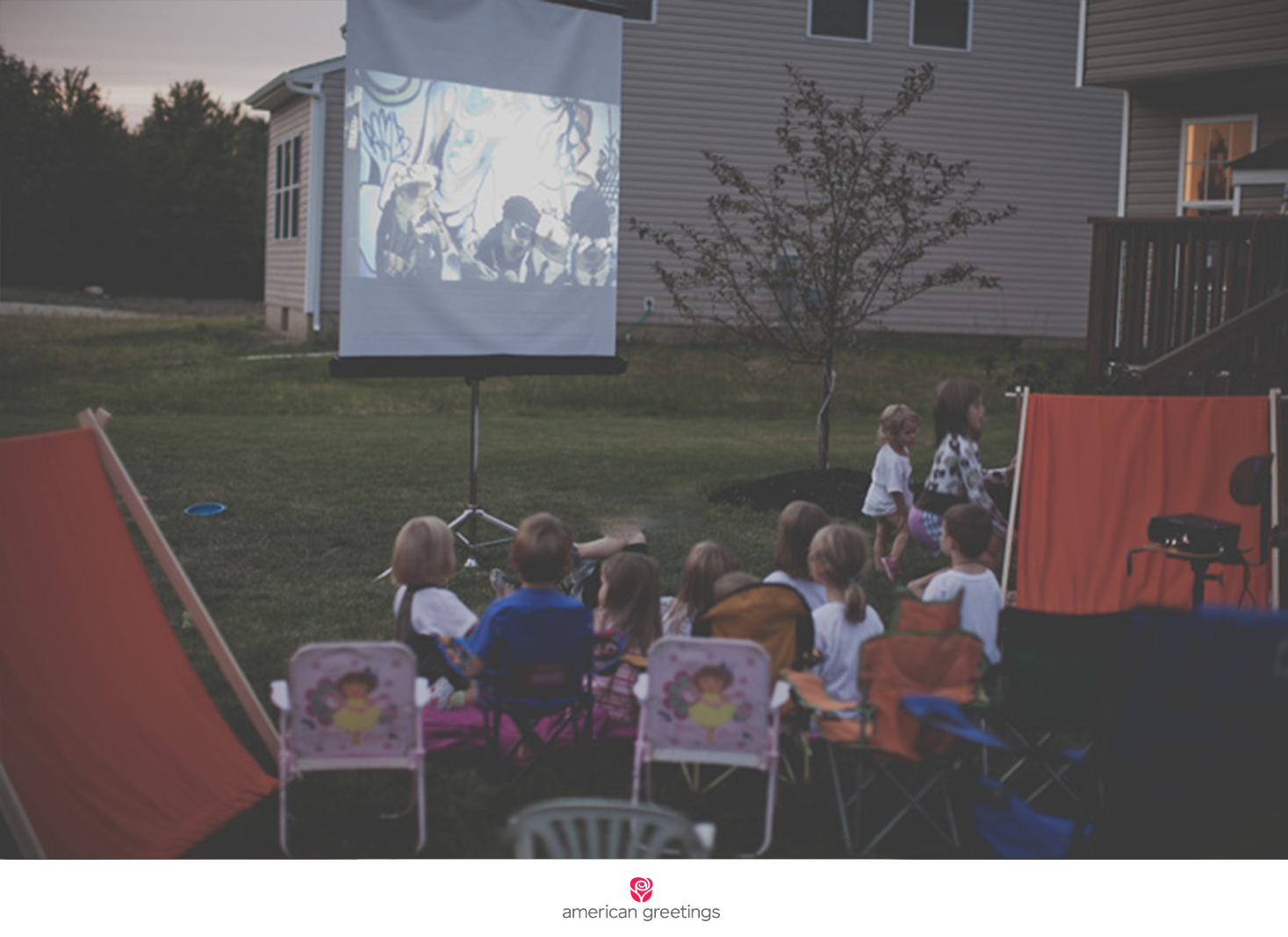 Kids snuggled up in sleeping bags, on lawn chairs, or in tents watching an outdoor movie