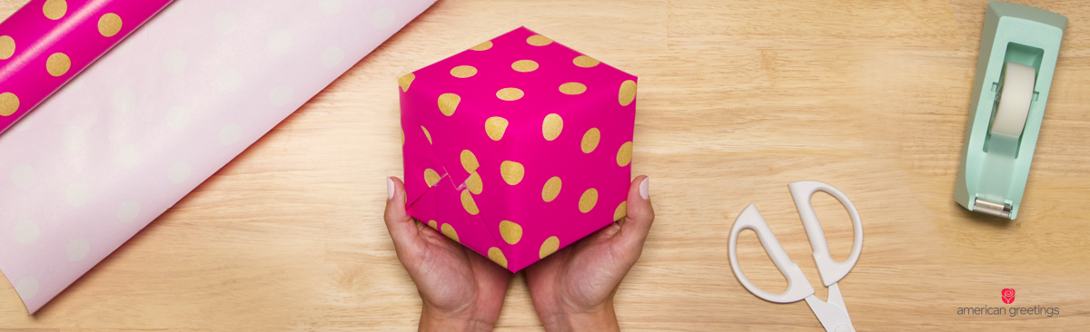 Image with hands holding the final result of the pink polka dotted wrapped gift