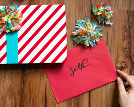 Striped white and red wrapped gift with pom poms next to a red card for