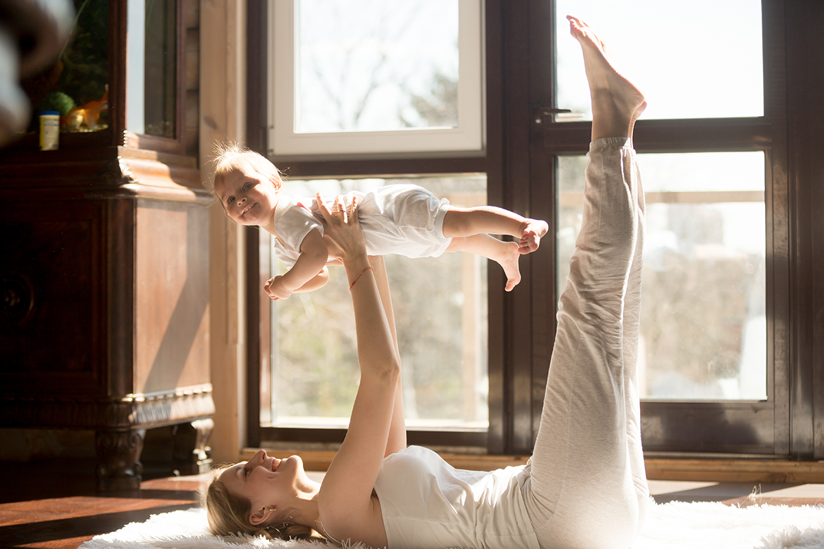 A happy mom playing and lifting her child in the air while laying on the floor.