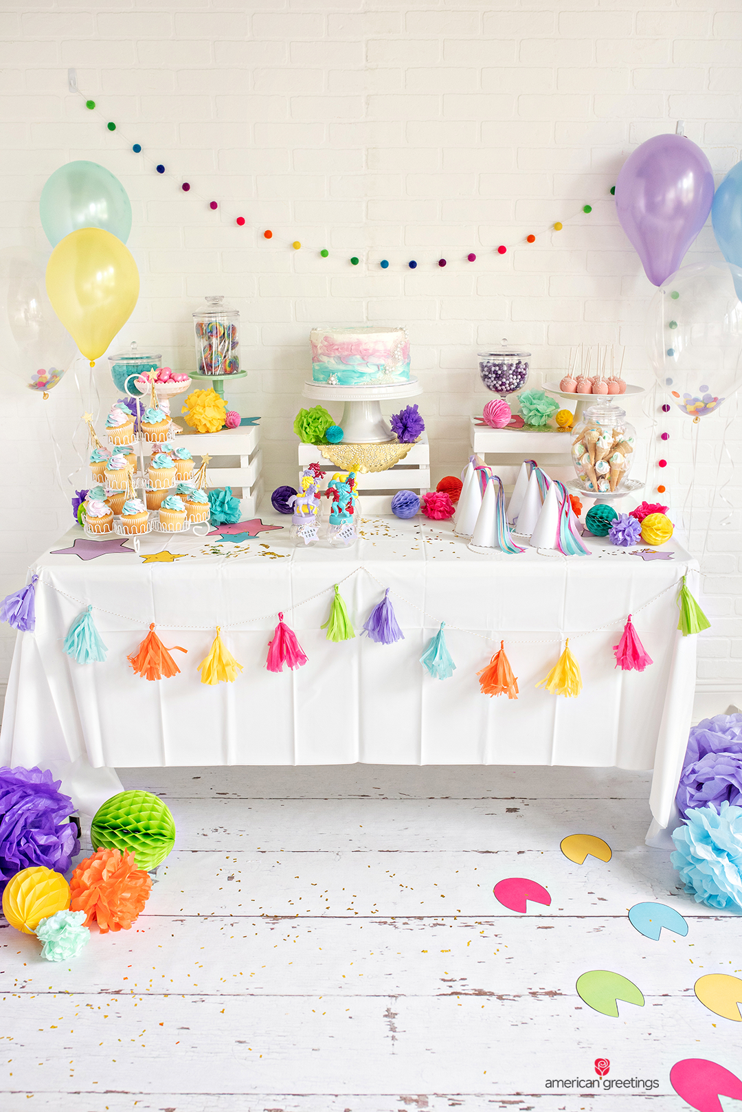 White Food Table decorated with a white tablecloth, tissue papper tassels and confetti-balloons with cupcakes, pink cake pops, gumballs and lollipops.