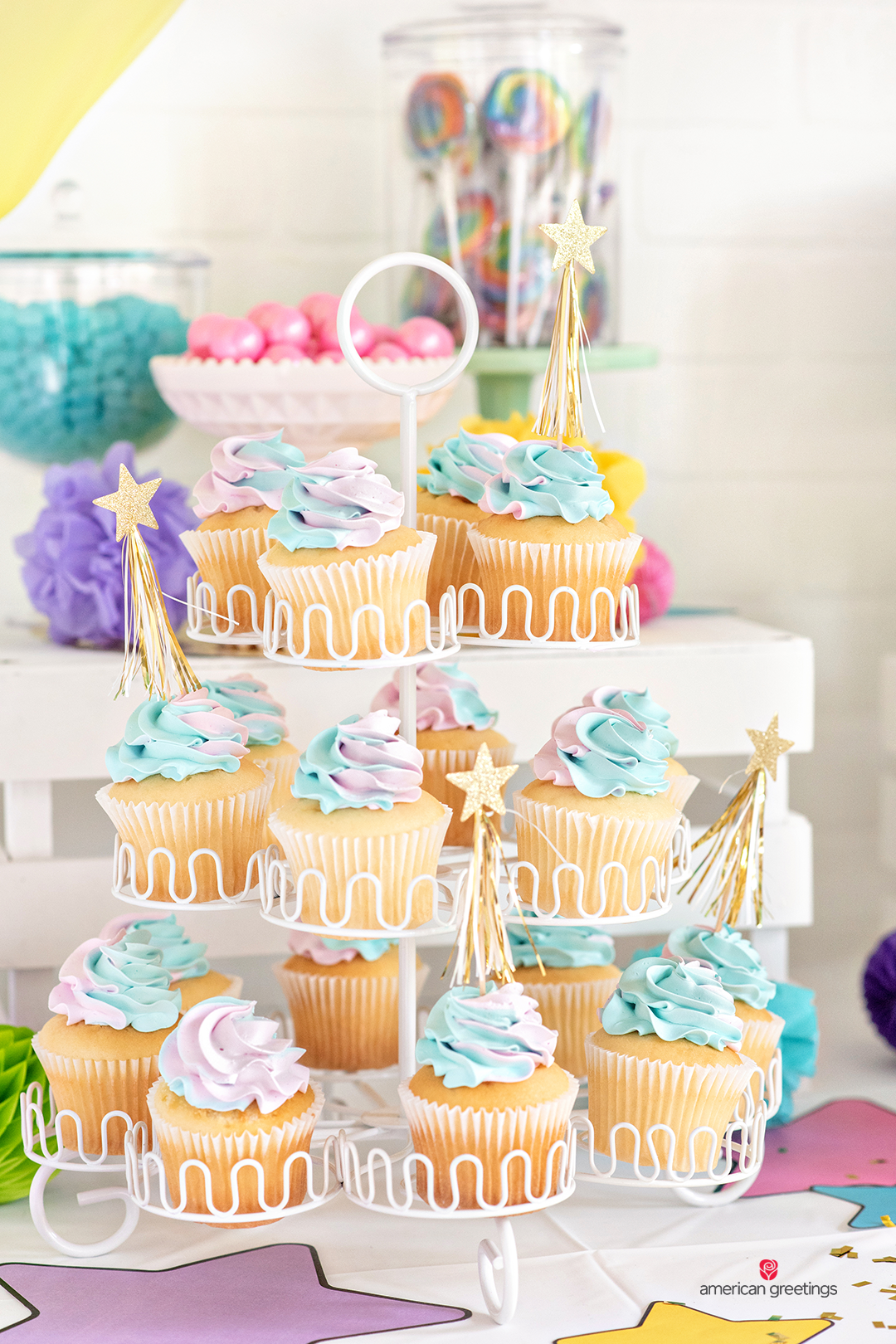 Cupcakes dressed up with gold tassel party picks placed on multiple hight levels.