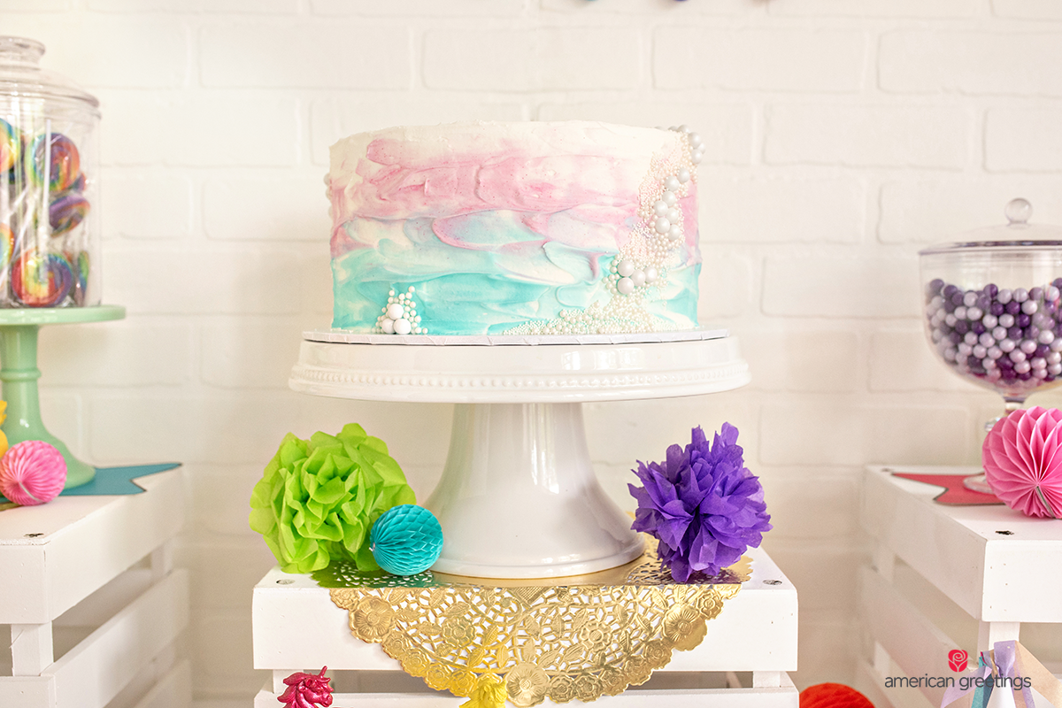 Colorful cake in a various shades of pink, purple and blue with a green, blue and purple tissue papper pom-poms at the base.
