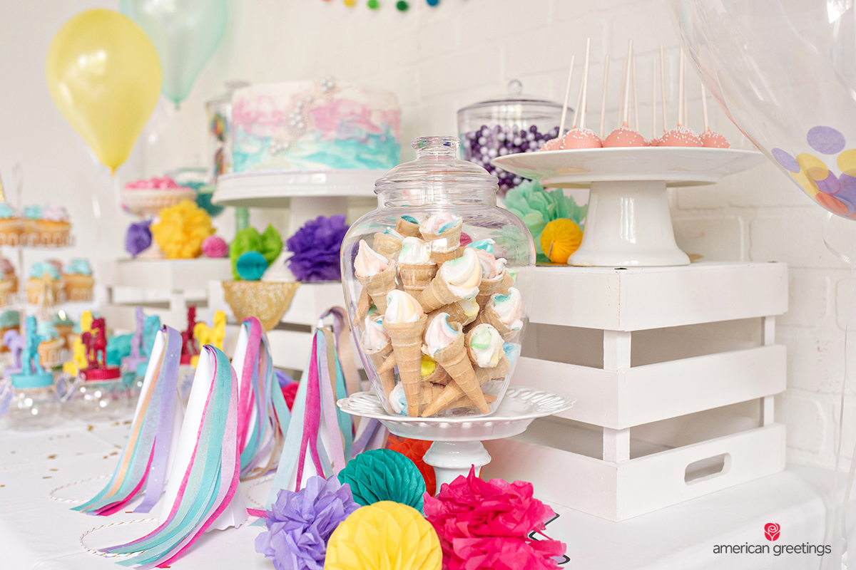 Marshmallow ice cream cones, purple candys and a colorful cake in the middle.