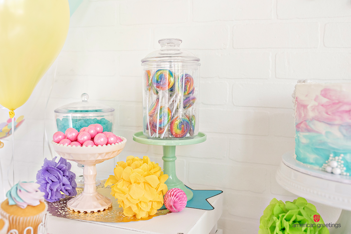 Large pink gumballs and a jar of rainbow lollipops on a white table surrounded by a lot of colorful decoration.