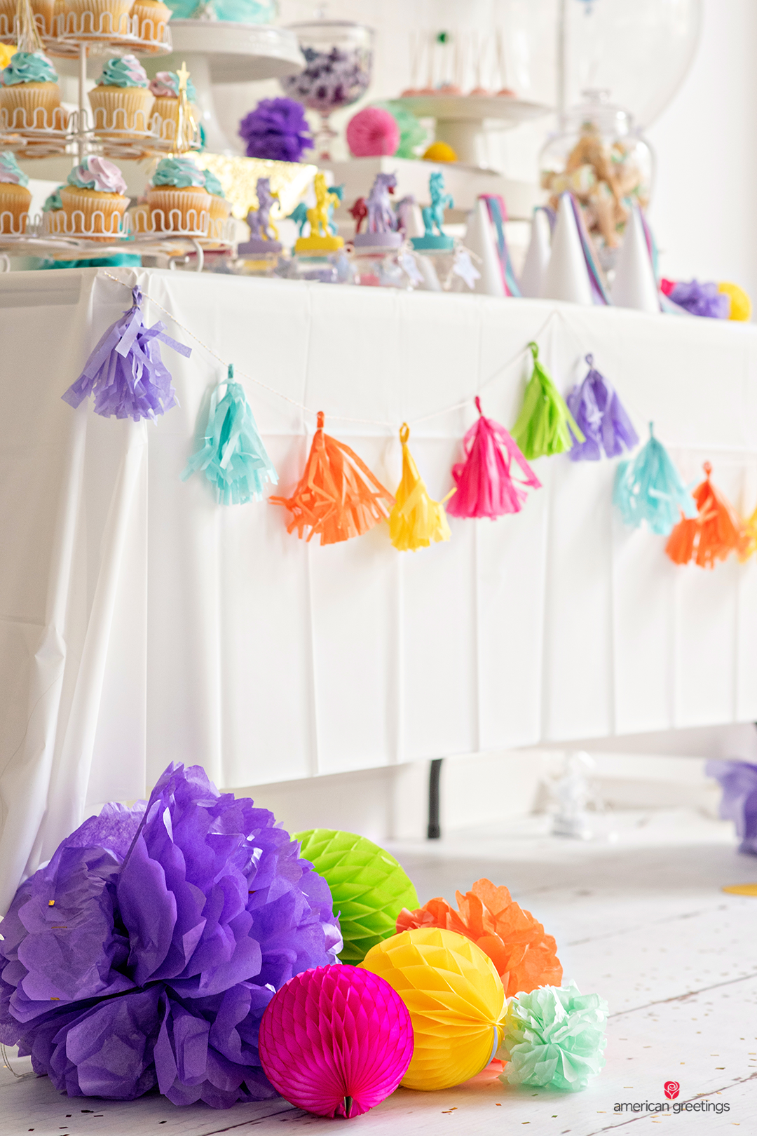 Colorful tissue papper pom-poms and honeycombs in various size next to a table on the floor.