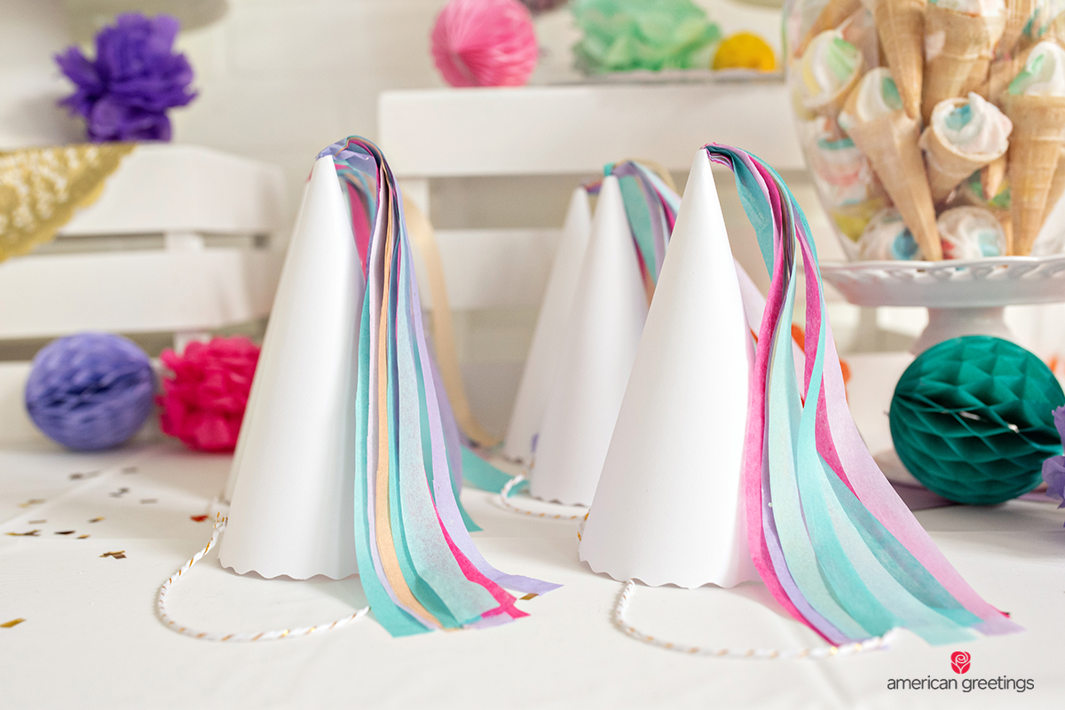 Unicorn horns made of paper cones with colorful flowing tassels, on a table near a jar filled with marshmallow ice cream cones.