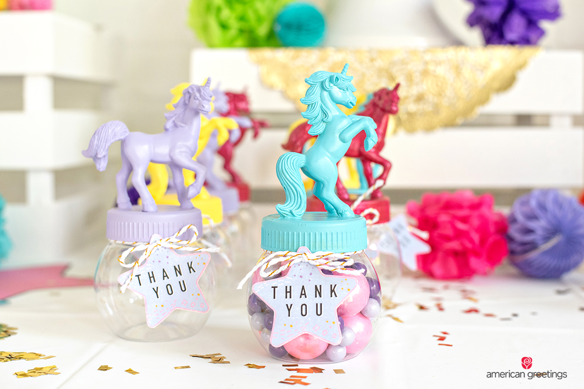 Mini acrylic jars with unicorn toys onto the top in various colors.