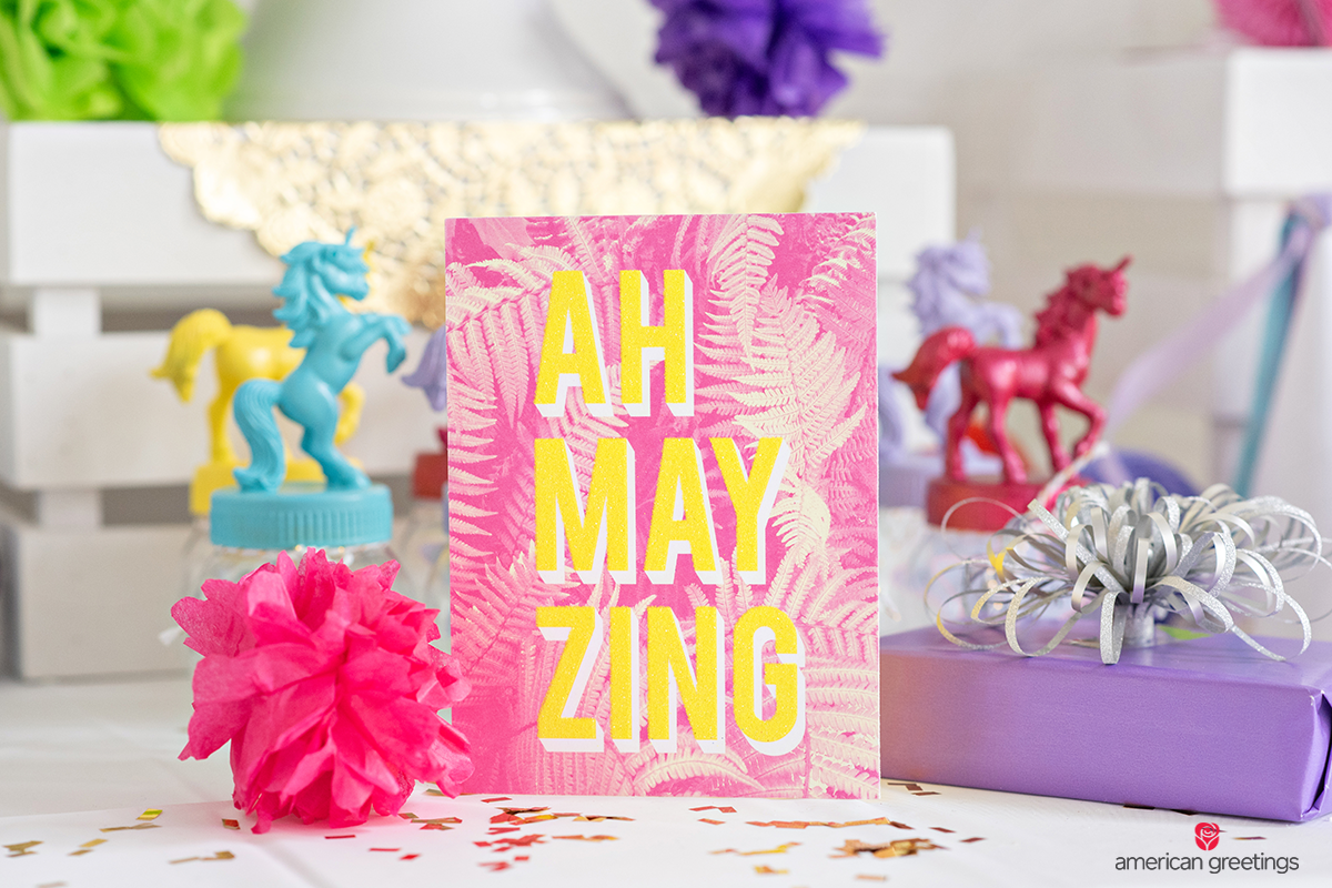 Pink greeting card near unicorn table decor.