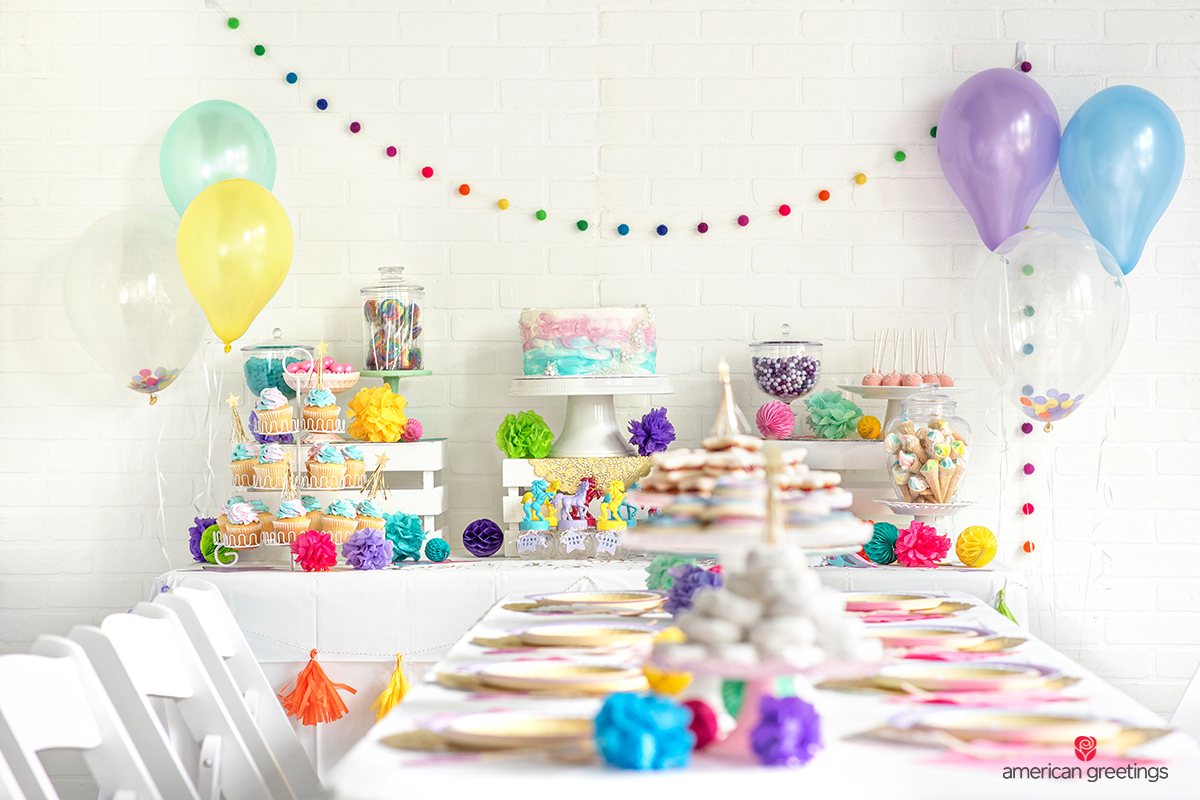 Dinner table setup with a white tablecloth and white chairs with a beverage spot in the background with a lot of cupcakes, candys, gumballs and lollipops.