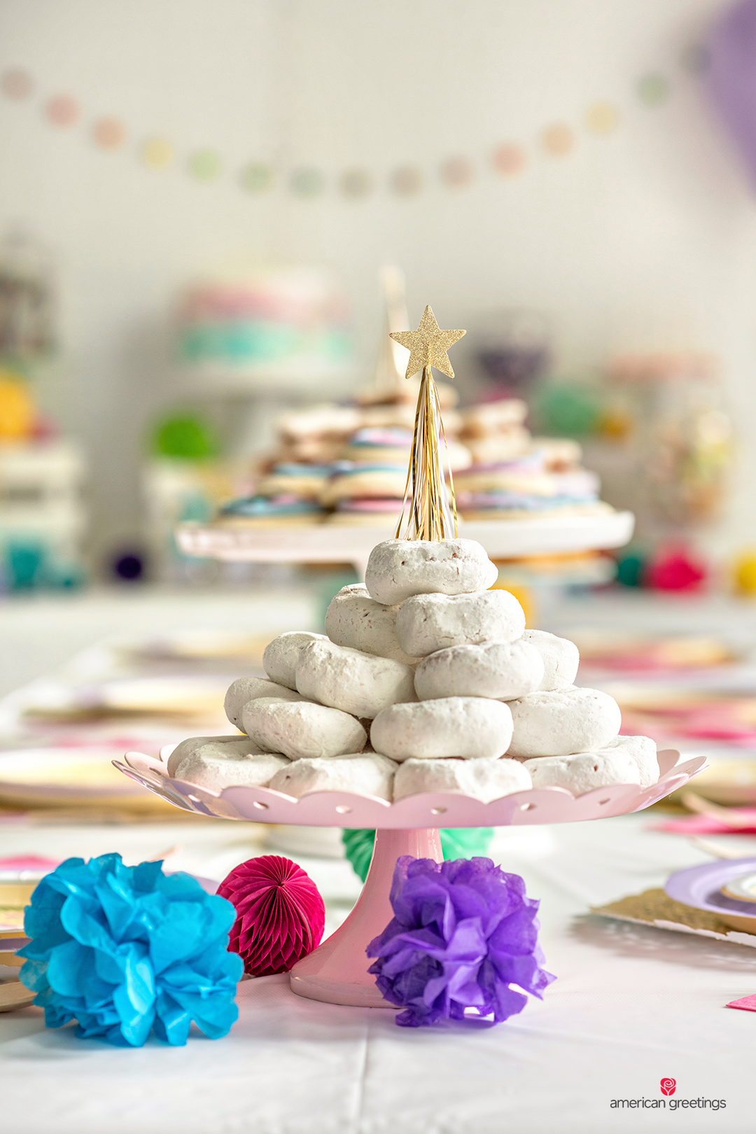 Powdered donuts on a pink plate with a blue, purple and red tissue papper pom-poms.