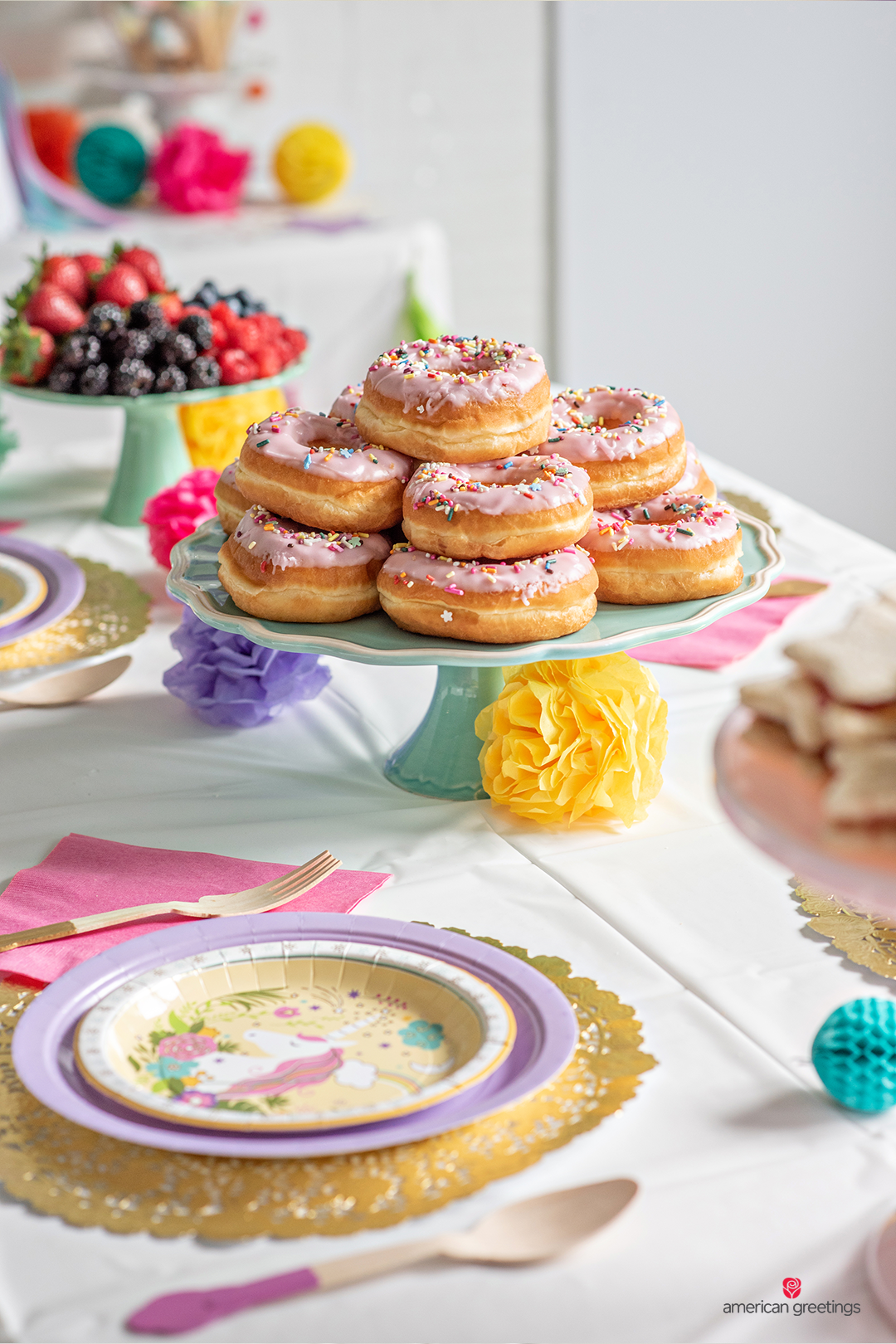 Sprinkled donuts near a fresh fruit plate on a dinner table setup.