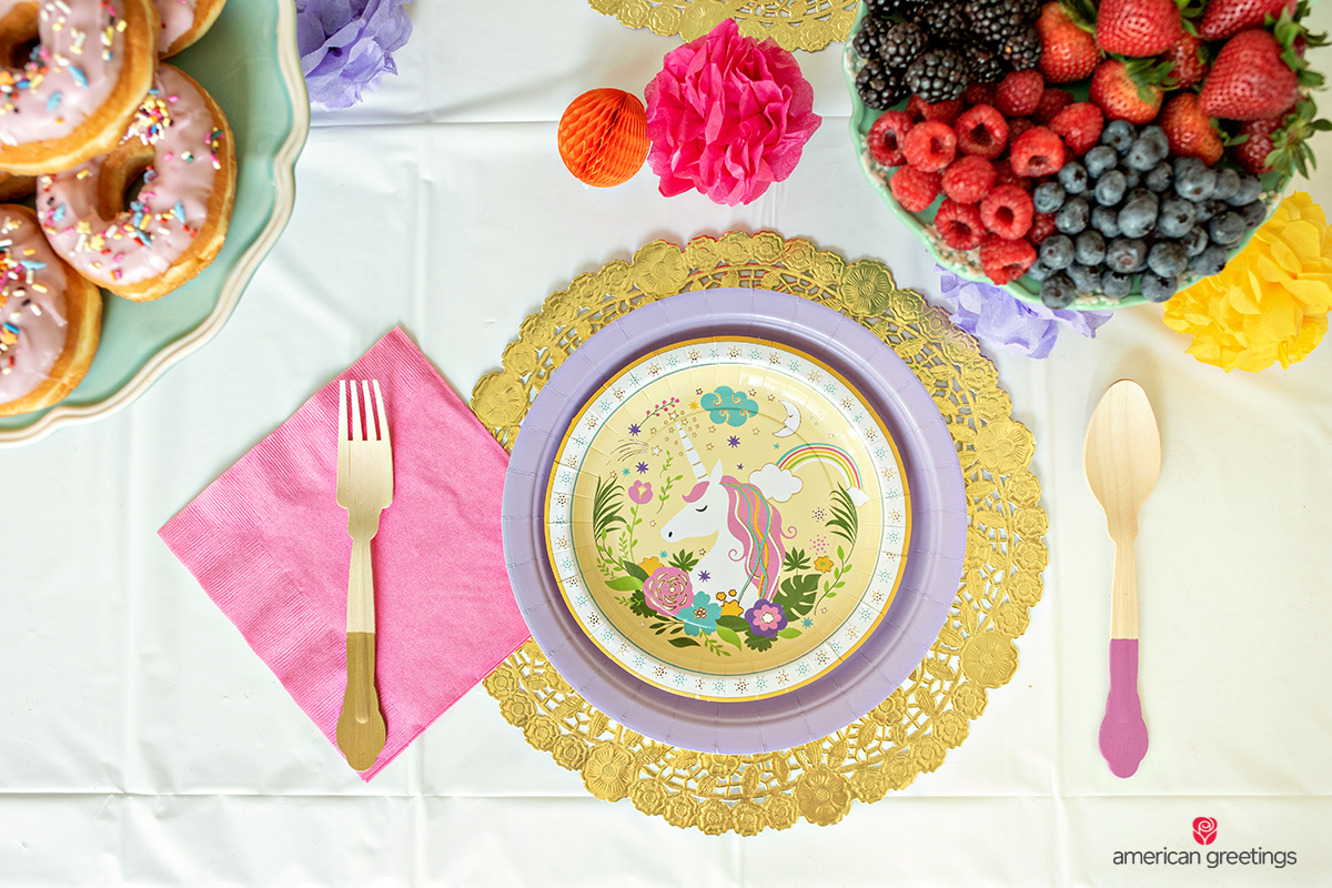 Unicorn layout dinner table with unicorn plates and gold wood utensils near some fruits and donuts plates.