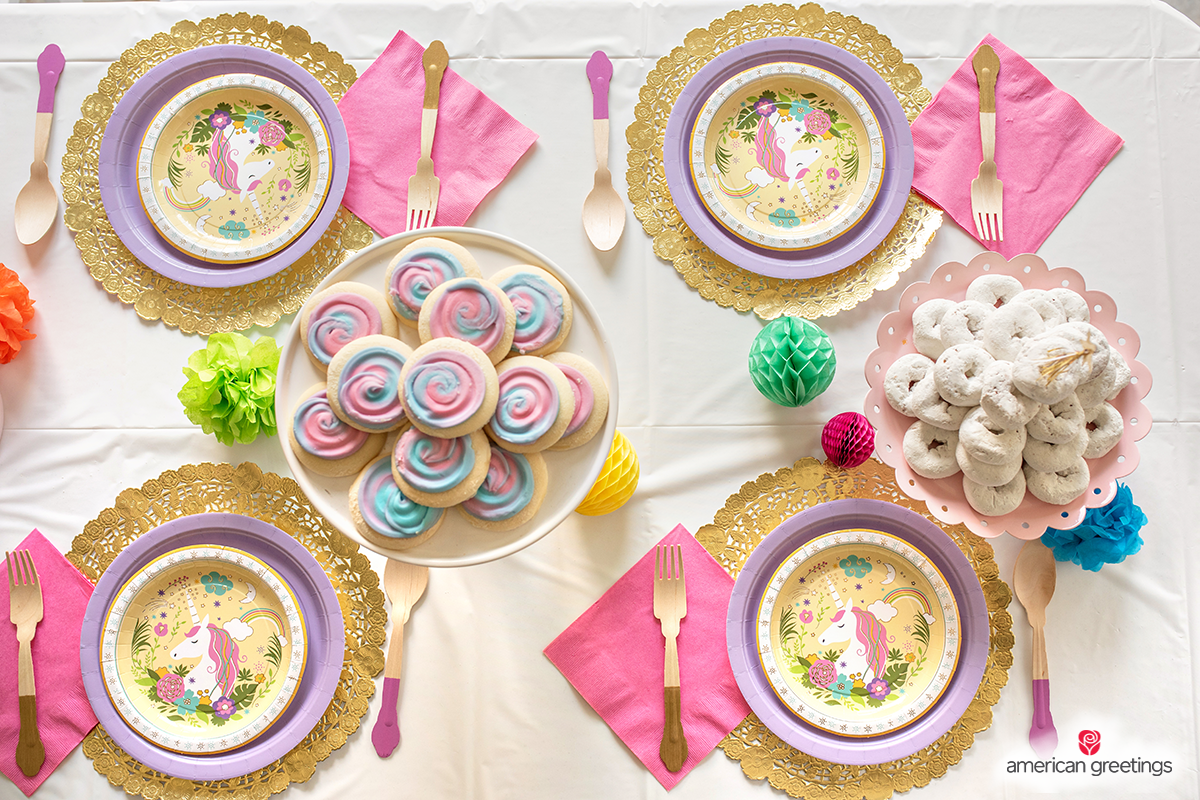 Top view  of rainbow cookies plates near the unicorn papper plates with pink cutensils and napkins.