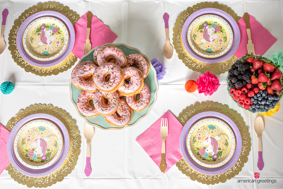 Top view of the table setup with sprinkled donuts anf fresh fruits near the papper unicorn plates.