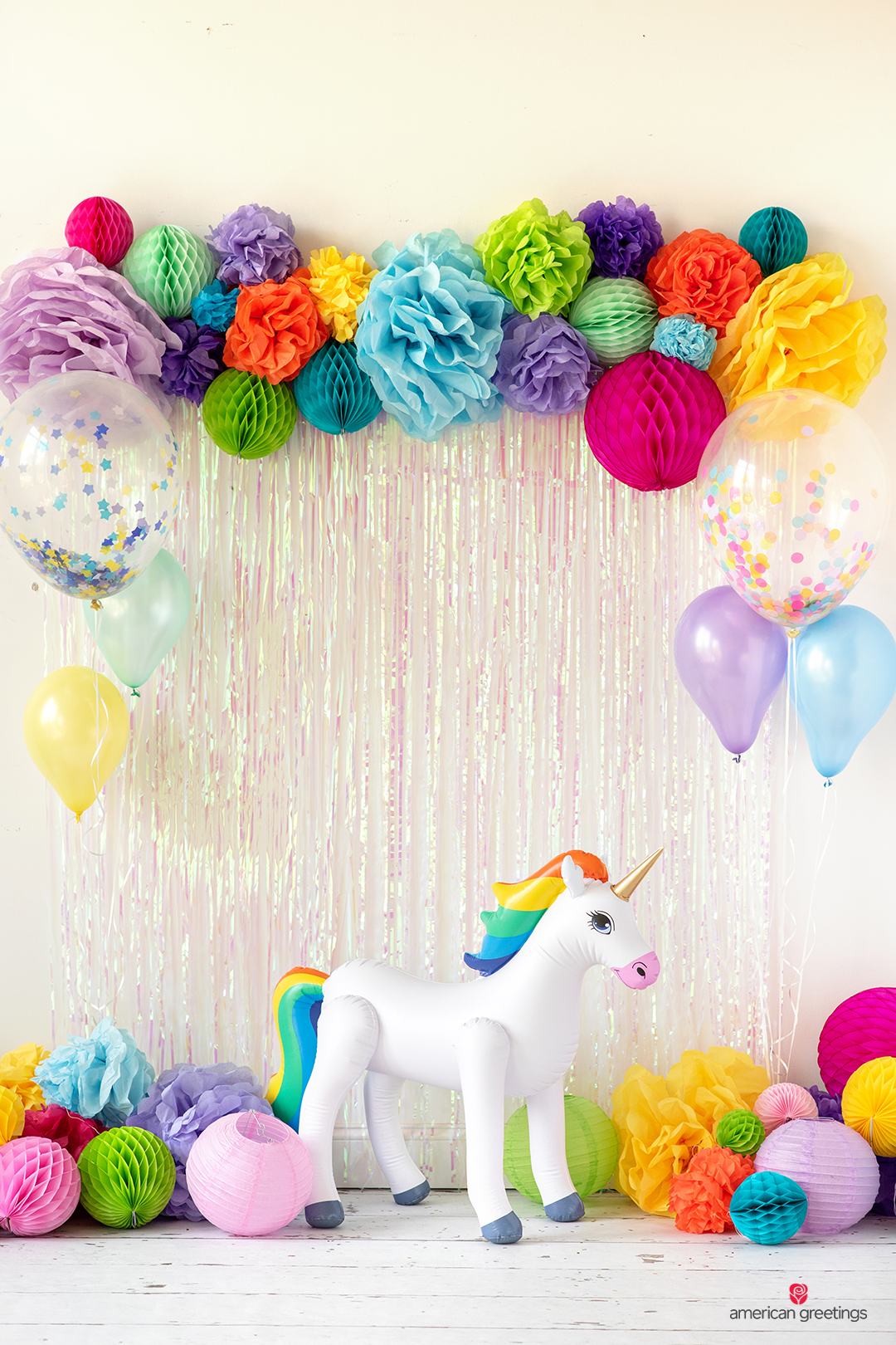 Tissue papper pom-poms and honeycombs in various colors and sized and with some oversized confetti-balloons and in the middle an inflatable unicorn.