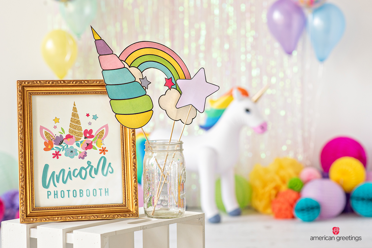 Golden unicorn photobooth frame near a jar with photo props and a lot od tissue papper pom-poms and honeycombs in various size and colores.