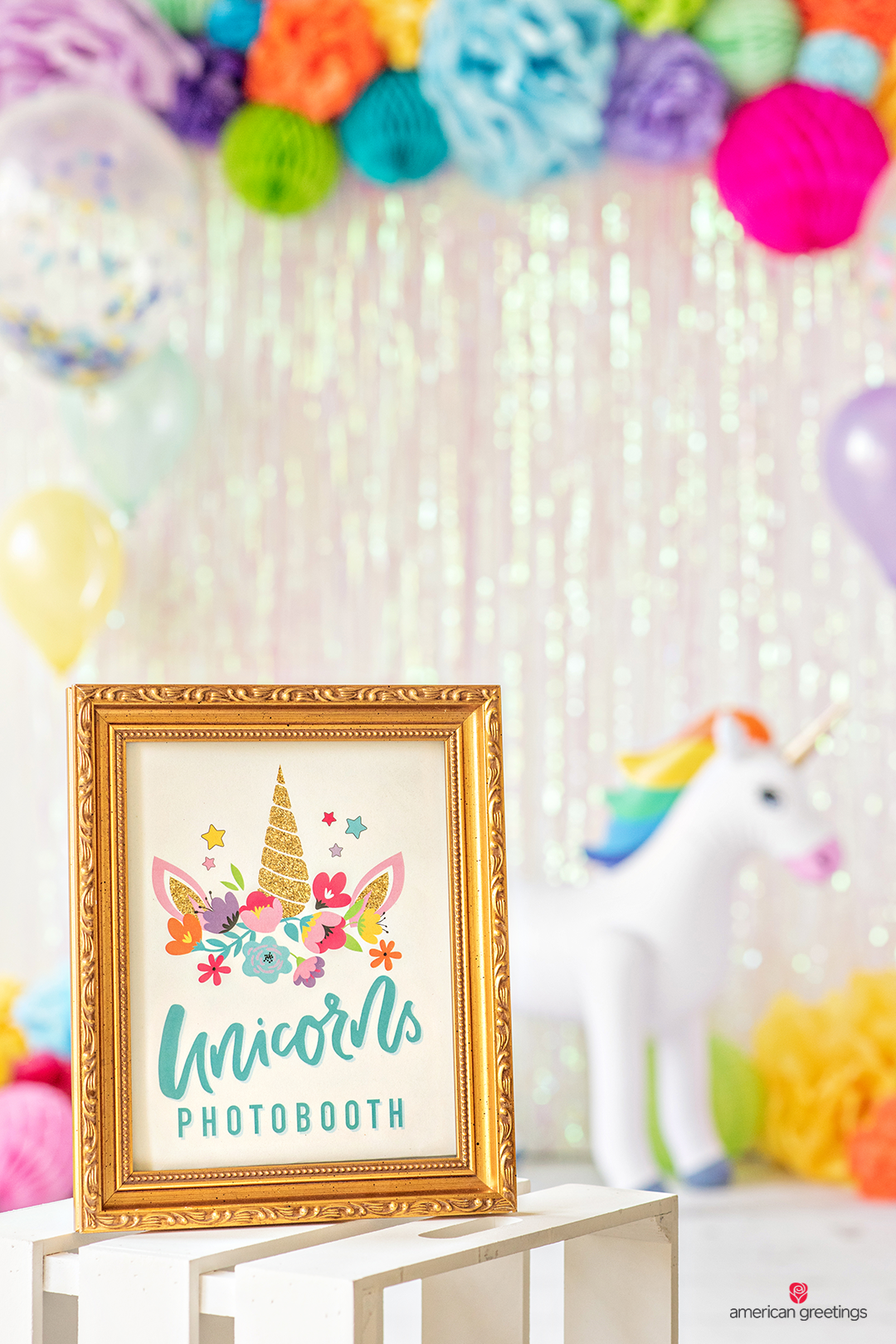 Gold Unicorn photobooth frame and in the background a garland of tissue pappper pom-poms and honeycombs.