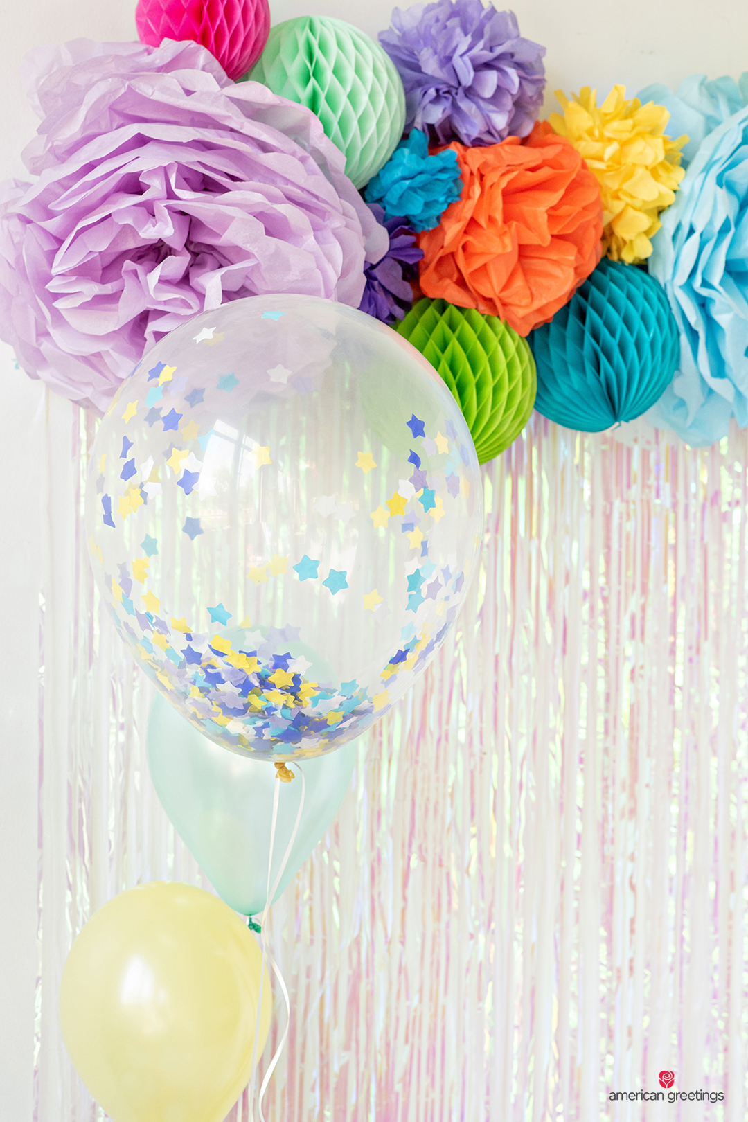 Oversized balloons near some tissue papper pom-poms in various colors and sizes.