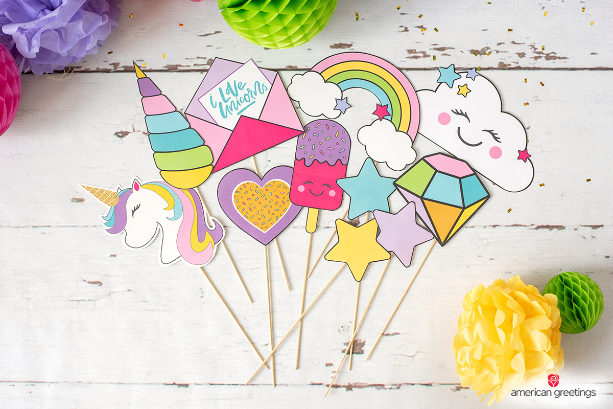 Unicorn, stars, rainbows and a lot of photoprops near some tissue papper pom-poms and honeycombs.