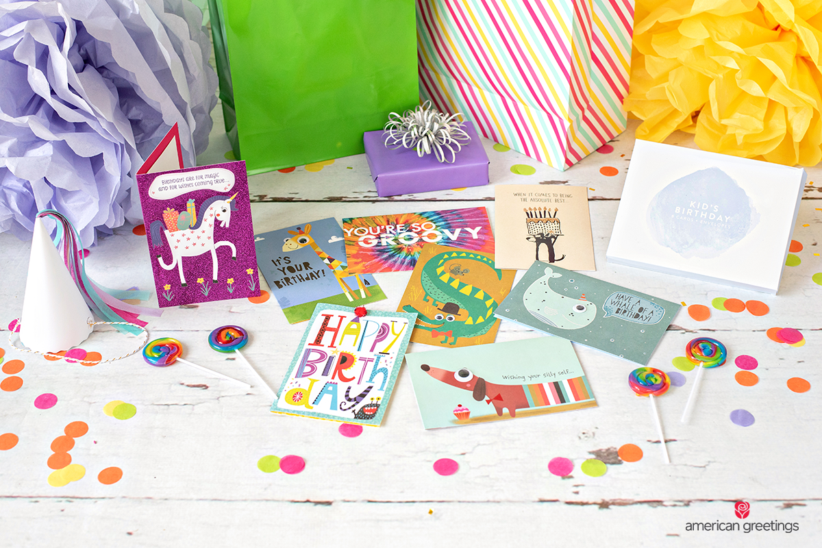 Colorful greeting cards near some pom-poms and a lot of confetti.