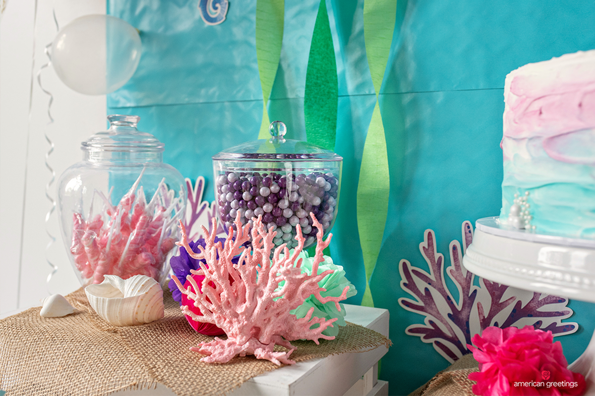 Various seashells and faux coral placed throughout the table to add interesting sprays of color